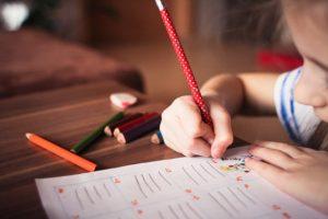 A little girl writing her homework.