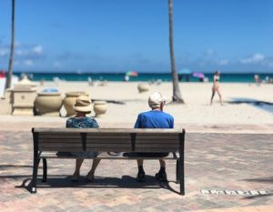 Two people sitting on the bench on a beach