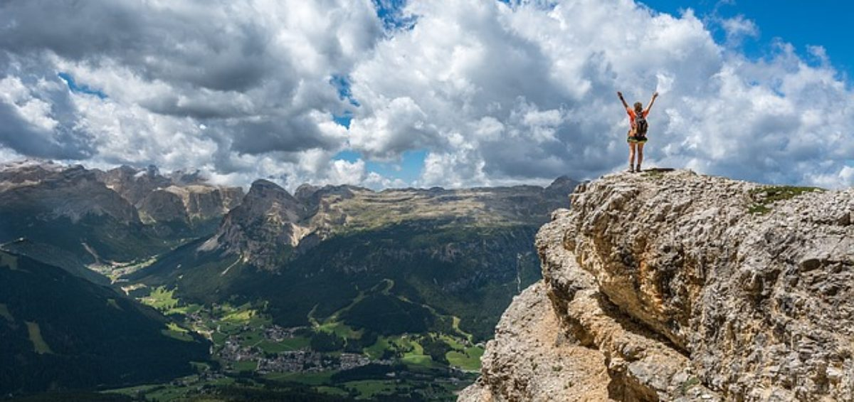 A person on the top of the mountain - Even climbing can be a way to reduce stress when moving