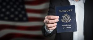 A man holds a U.S. passport in his hand, ready for moving to Florida