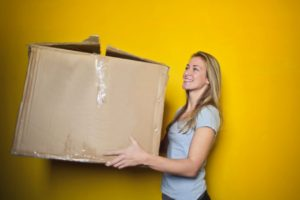 woman carrying a moving box to pack and move fragile items
