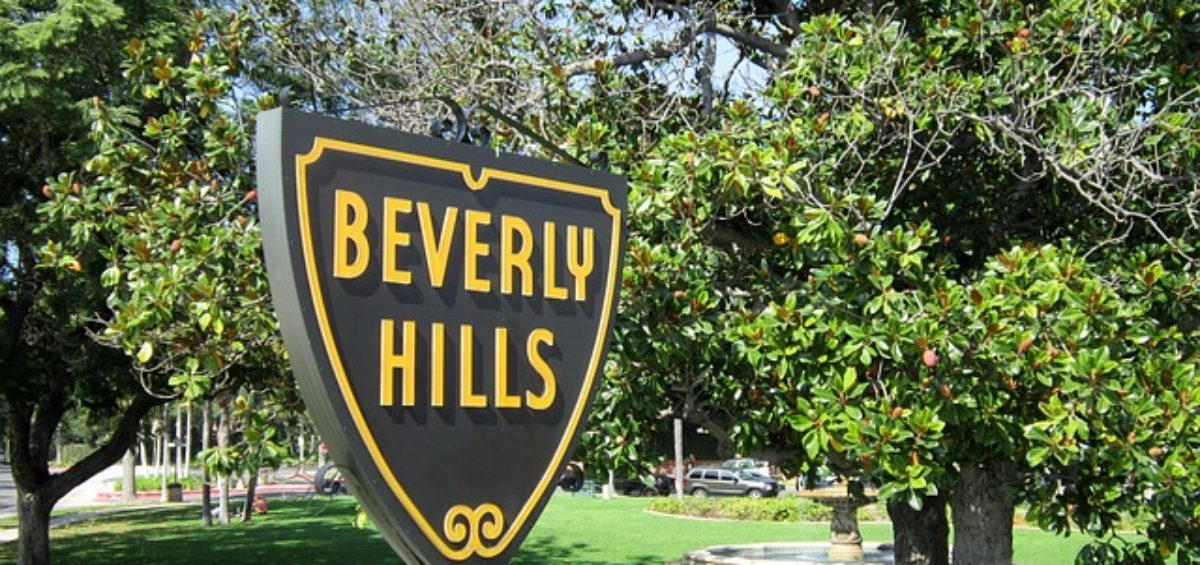 A sign in a park saying 'Beverly Hills', representing living in Beverly Hills with a dog.