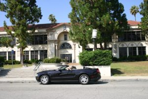 A convertible parked in front of a Beverly Hills mansion.