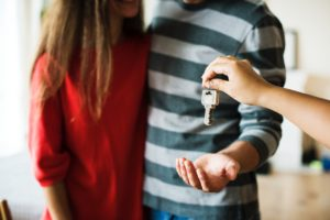 A person giving keys to a couple - now they need to adapt to life in California
