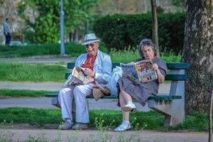 Seniors sitting in a park after moving.