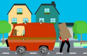 A mover by a moving van carrying the box.