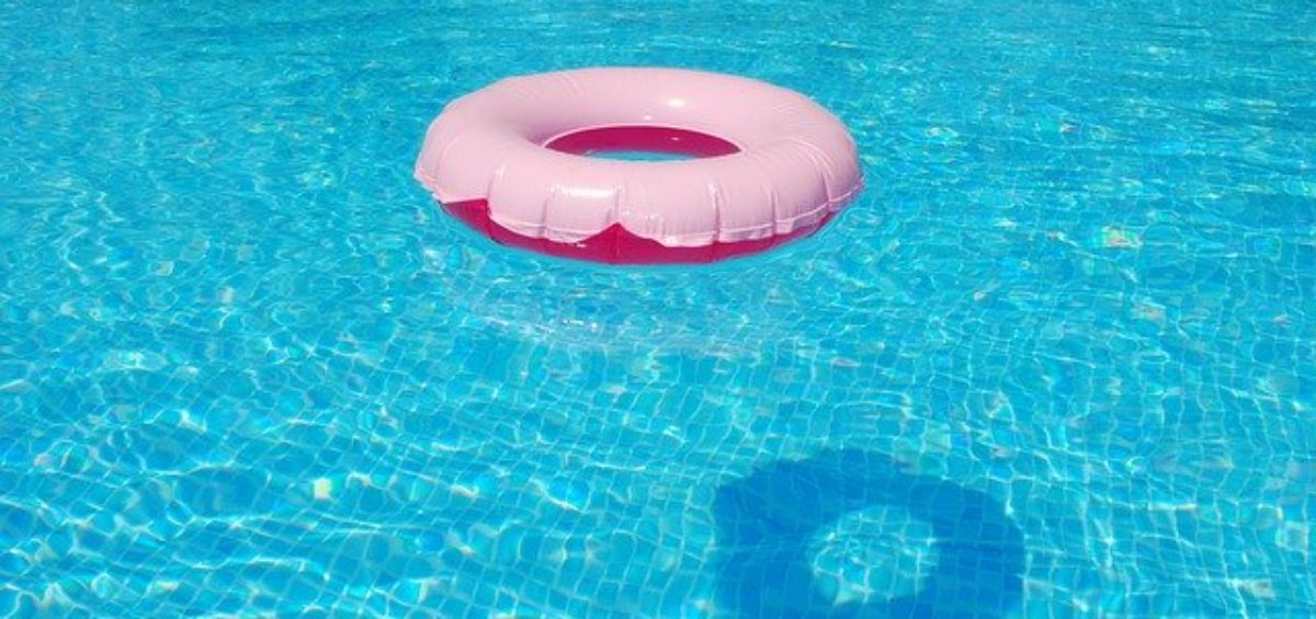 A tire floating in a clean pool belonging to someone who's applied the tips for pool maintenance.
