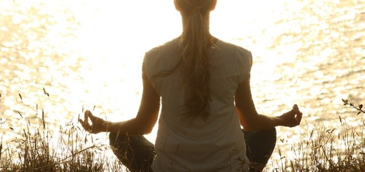 A woman meditating as a proper strategy for last-minute de-stressing before your big move.