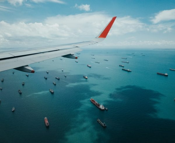 A airplane flying over the ocean with a lot of ships beneath it which symbolizes overseas trading between California and Bahrain.