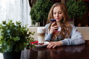 A girl using her mobile to browse the best  locations to set up a coffee shop