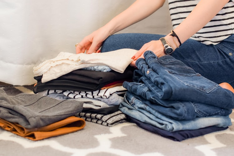 A woman folding her clothes and getting ready for her move.