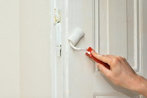 A man painting the door as renovation is one of the things you should include in your budget plan for buying a house.