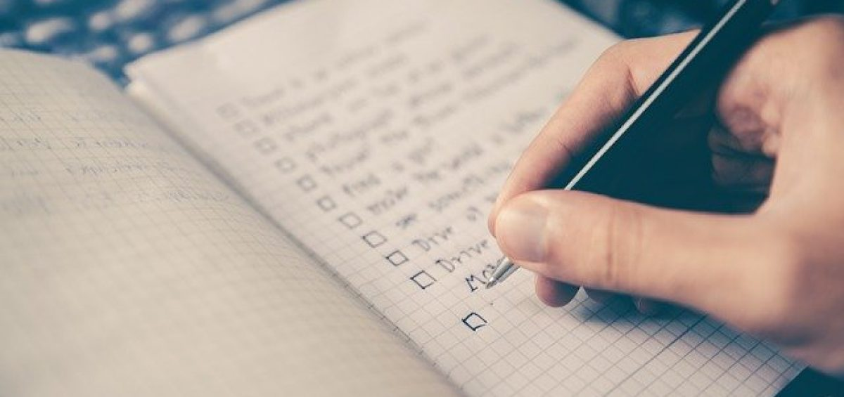 A man holding a pen and writing a moving essentials checklist
