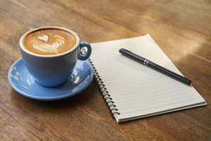 A coffee, a notebook, and a pen.