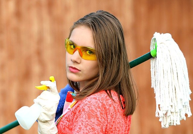 A girl with goggles, holding a mop and spraying bottle, needed elements of a moving essentials checklist.