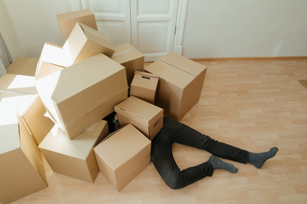 A man lying under a pile of cardboard boxes after moving into your new home.
