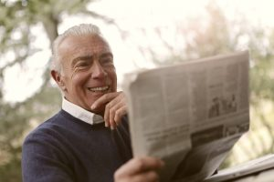 An older man reading an article in the newspaper about where do senior citizens have bigger benefits