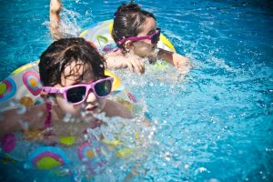Children enjoying the pool after you baby-proof your yard.