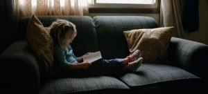 Girl sitting on the sofa reading the book