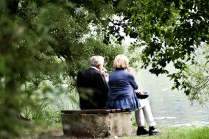 Two elderly people sitting on the bench and watching the lake