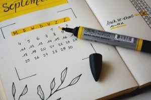 A calendar with a pen. One of the tips for moving during the summer season says you should hire movers ahead of time.
