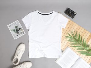 A white T-shirt, a camera, an open book, and some shoes.