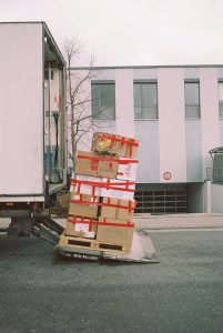 A pile of packed cardboard boxes being loaded onto a moving tuck after buying a home on the East Coast