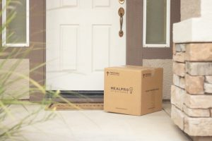 Packed cardboard box in front a front door of a house.